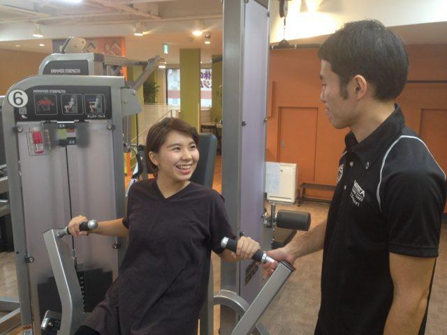 トレーニングマシンに乗った女性と男性が談笑している