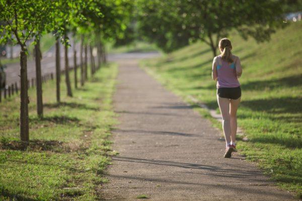 道を走るタンクトップ姿の女性