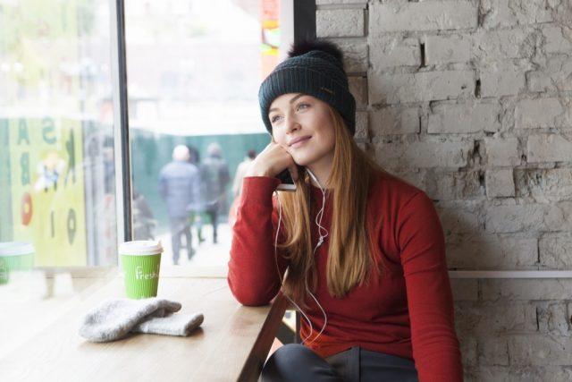 窓際でくつろぐ赤いニットを着た白人女性