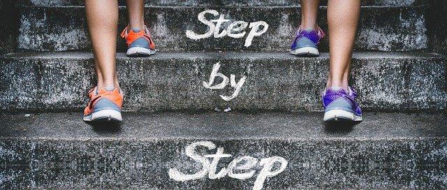 階段と人の足 「Step by Step」の文字