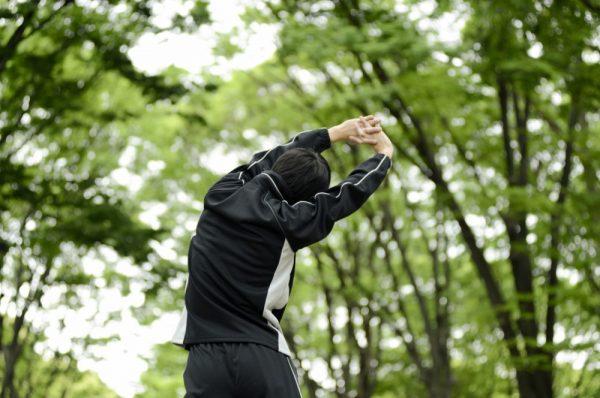 森の中を背伸びしながら歩く黒ジャージ姿の男性
