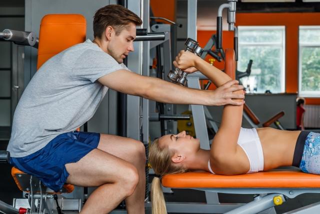 女性にトレーニング指導する男性トレーナー