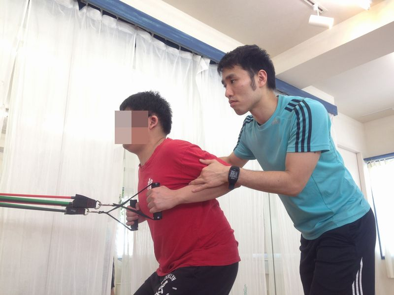 チューブを使った肘を引く運動を指導する男性