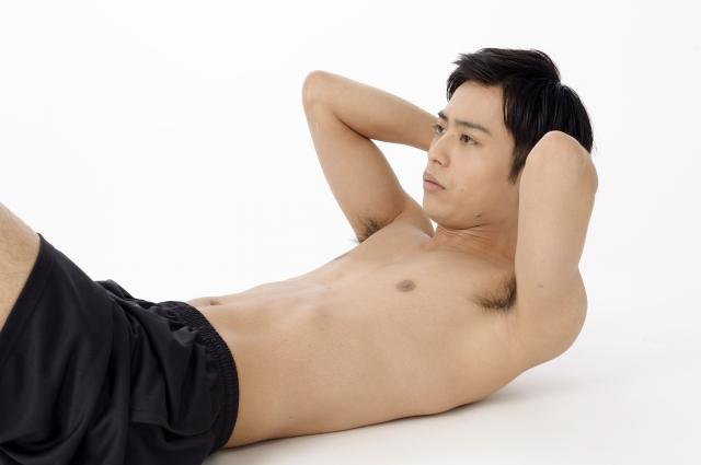 腹筋をする上半身裸の男性