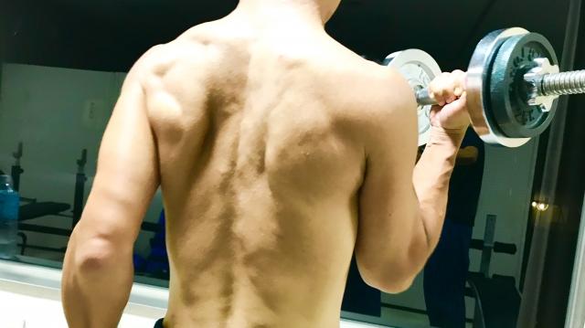 アームカールをする上半身裸の男性