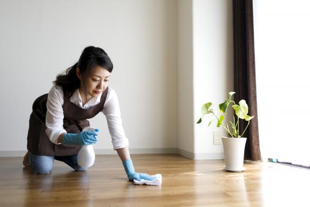 雑巾を左手に床掃除をするエプロン姿の女性