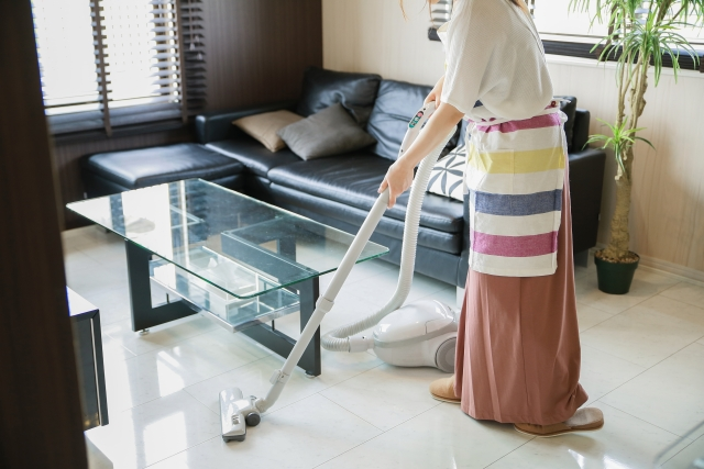 掃除機をかけるロングスカートの女性