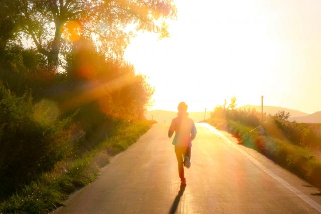 太陽に向かって公道を走るランナー