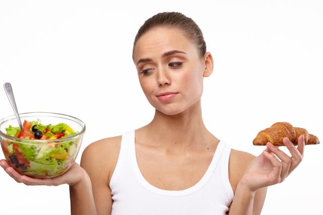 サラダとクロワッサンを両手にもつ女性