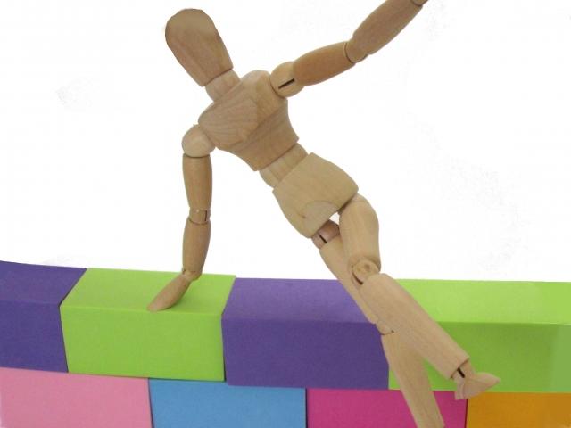 カラーボックスでできた塀を飛び越える木製人形