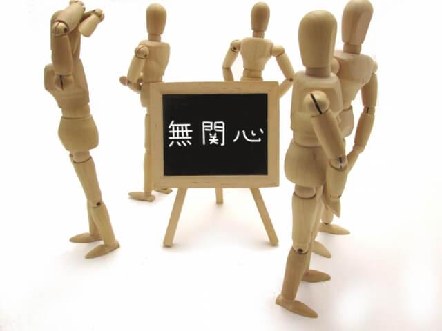 「無関心」と書かれた黒板と逆方向を見る木製人形5体