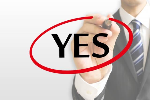 「YES」の言葉をかくスーツ姿の人