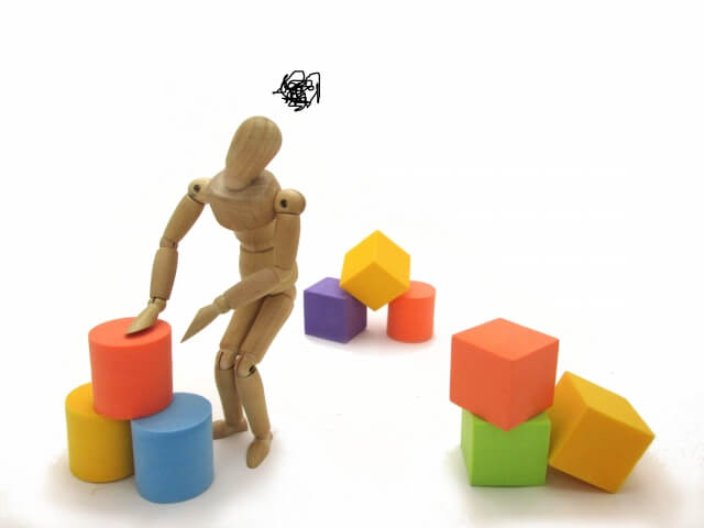 崩れたブロックを触る木製人形