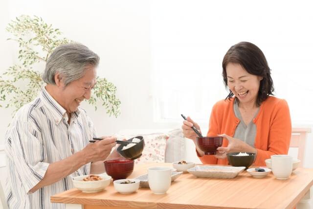テーブルで食事するシニア夫婦