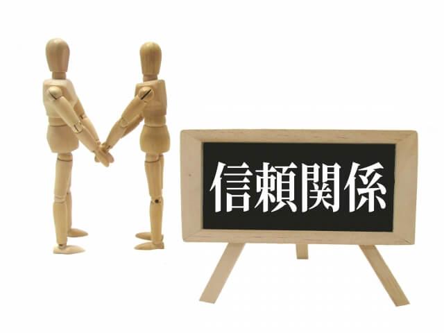 「信頼関係」の文字が書かれた黒板と握手する木製人形