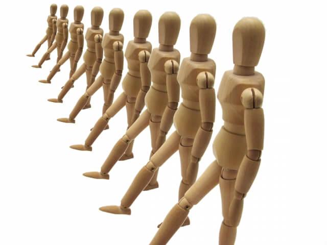 列に並び右足を同時に前に出す木製人形