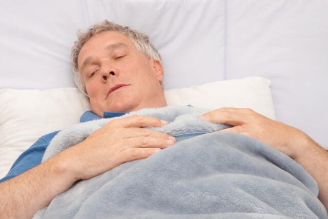 布団をかけて寝ているシニア男性