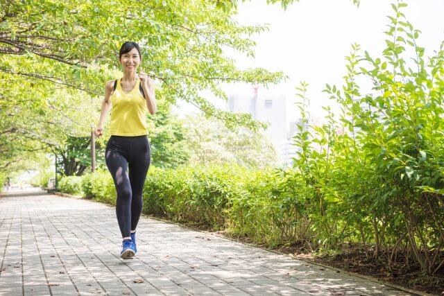 緑の中を走るスポーツウェア姿の女性