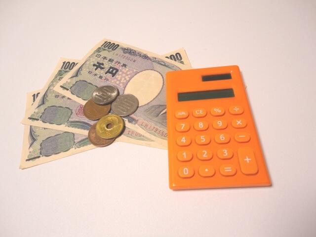 オレンジ色の電卓と3枚の千円札と小銭