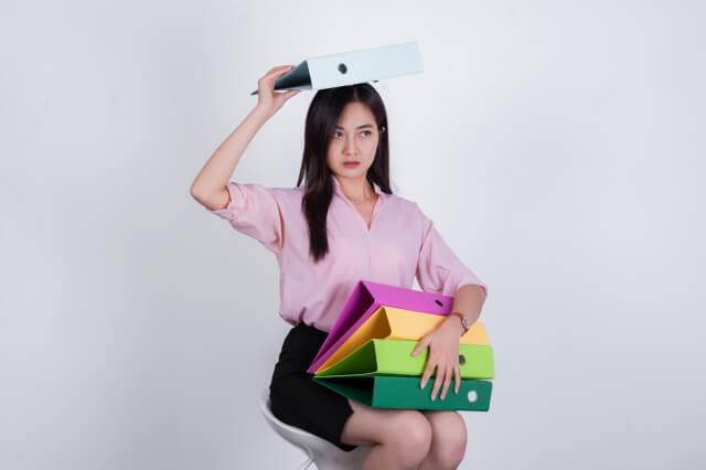 ファイルを頭の上と膝の上に載せる女性