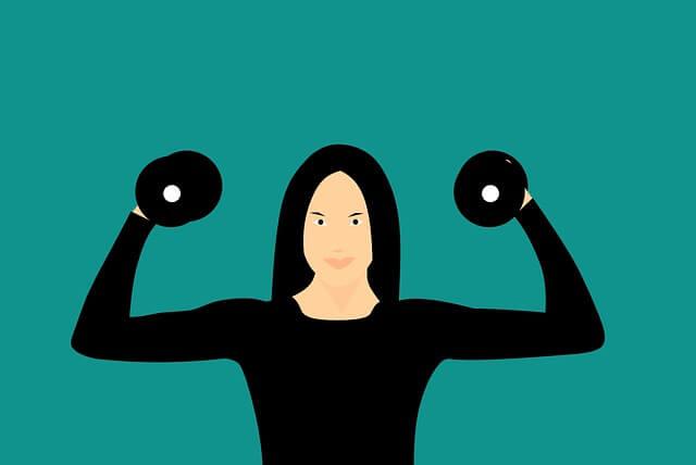 両手にダンベルを持ち力こぶをつくる女性