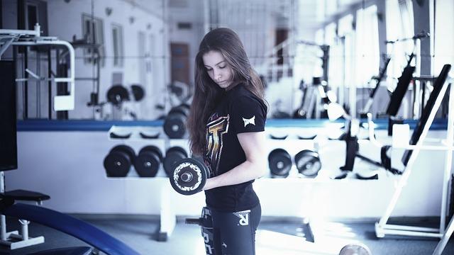 ダンベルを持つ黒いTシャツ姿の女性