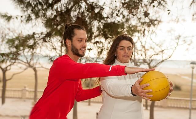 ボールを持つ女性の肩に手をかける男性