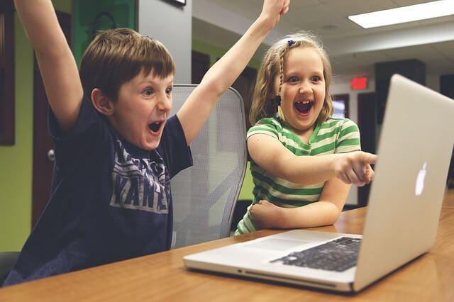パソコンの画面を見て喜ぶ二人の子供