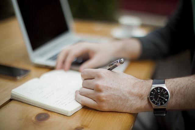 モバイルパソコンと手帳と人間の手