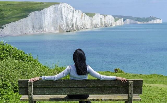 ベンチに座り海を眺め女性