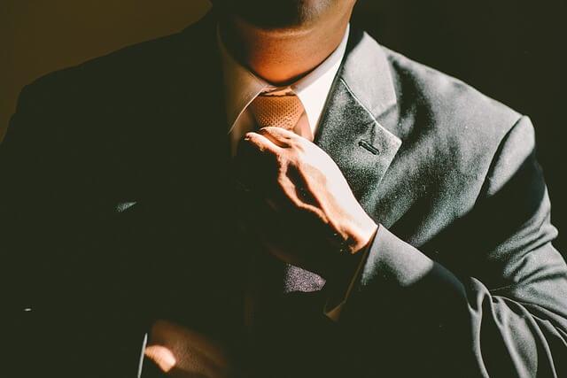 ネクタイを締めるスーツ姿の男性
