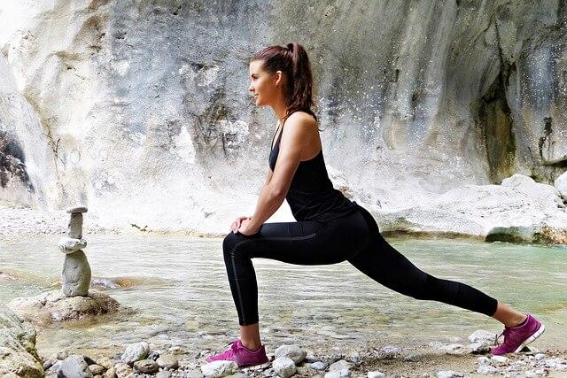 河原で足を前後に開き屈伸する女性
