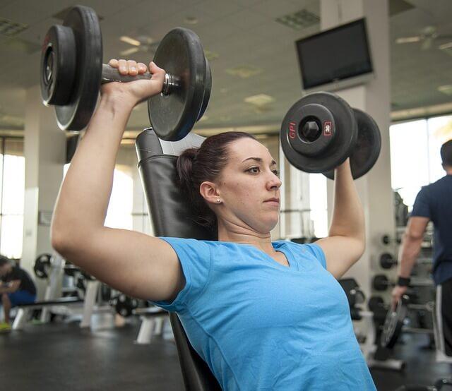 ダンベルを両手で持ち上げるタンクトップ姿の女性