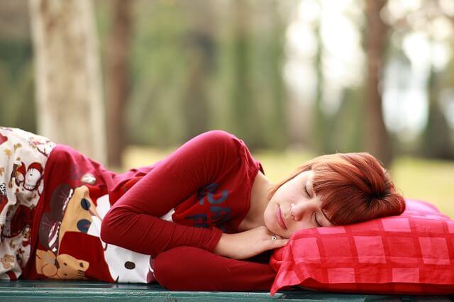まくらにあたまをのせて横向きに眠る女性