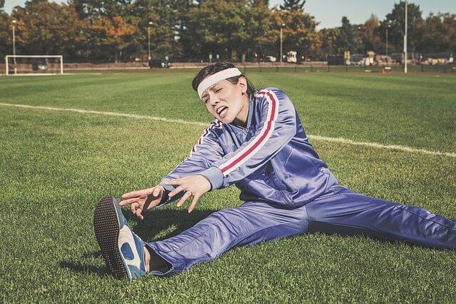 芝の上で苦しそうに前屈するジャージ姿の女性