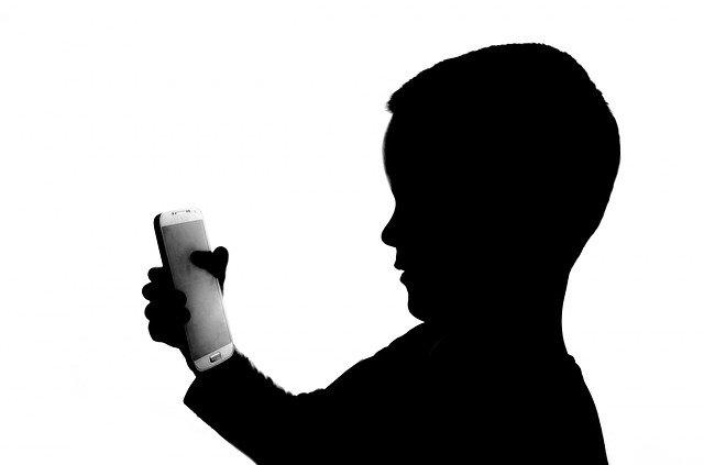 スマホを見つめる子供のモノクロ画像