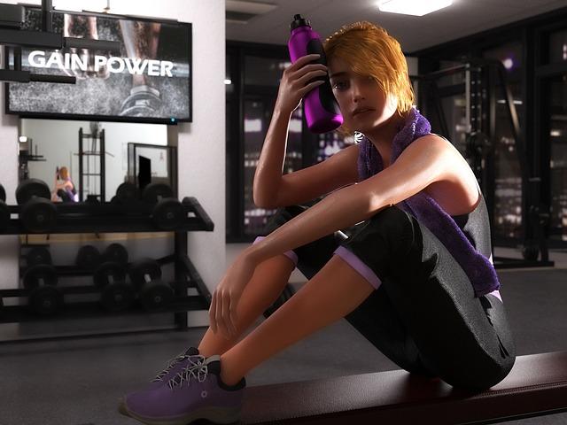 体育座りをしながら飲み物を額に当てる女性
