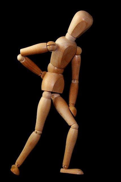 腰を抑える木製の人形
