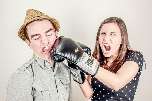 ボクシンググローブをつけて男性の顔にパンチする女性