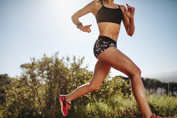 日差しを浴びながら走る女性