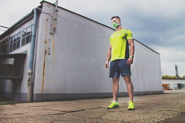 廃屋の前に立つマスク姿の男性