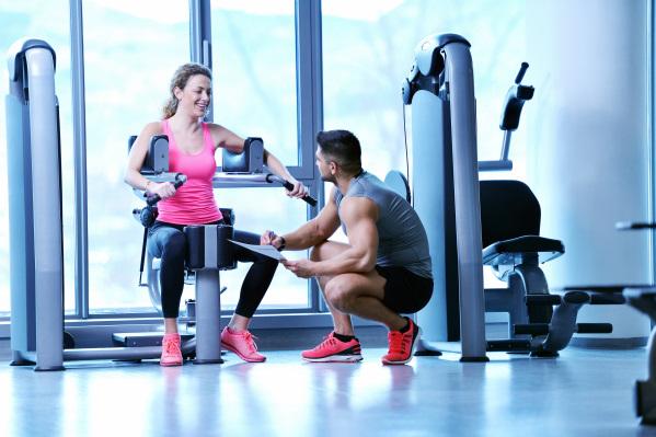 トレーニングマシンに座る女性と男性