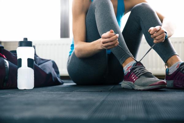 床に座り靴ひもを結ぶ女性