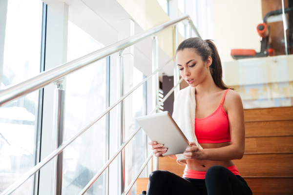 階段に座りタブレットPCを見る半袖の女性