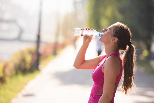 水を飲むタンクトップの女性