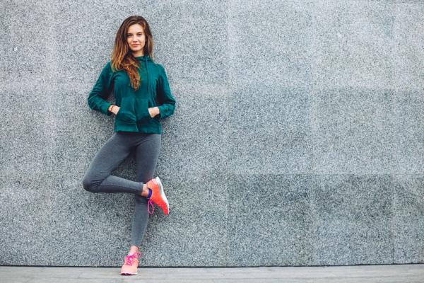 壁に寄り掛かりながら足を組む、立ち姿の女性